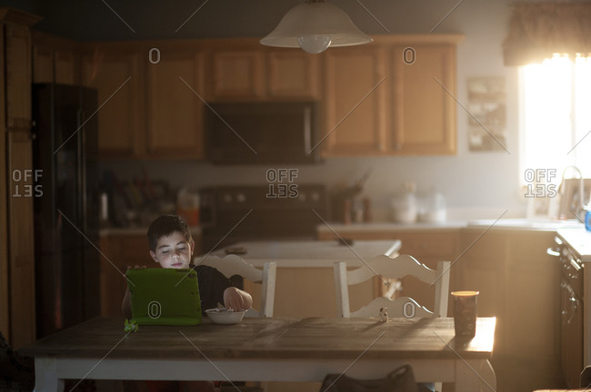 Young boy eats breakfast while watching his tablet in the kitchen