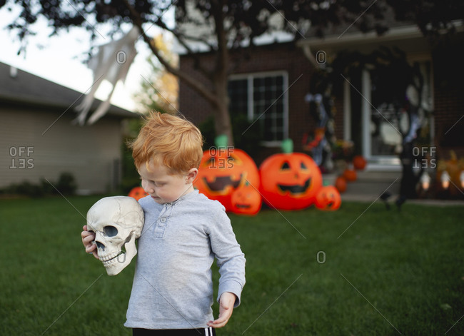 Toddler holding skeleton head in front of outdoor Halloween decor