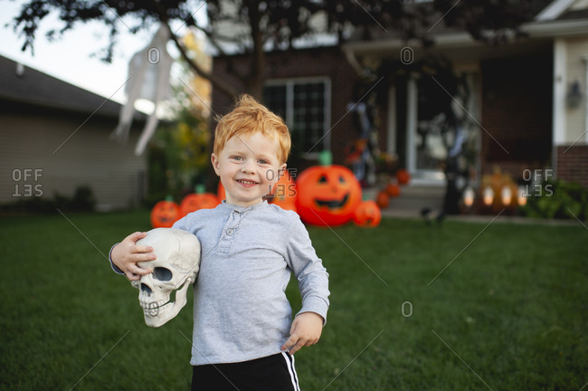 Toddler boy smiling while holding Halloween decor in front yard