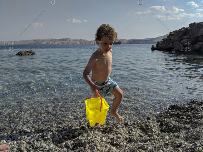 Little boy carrying a bright yellow pale of water near the sea