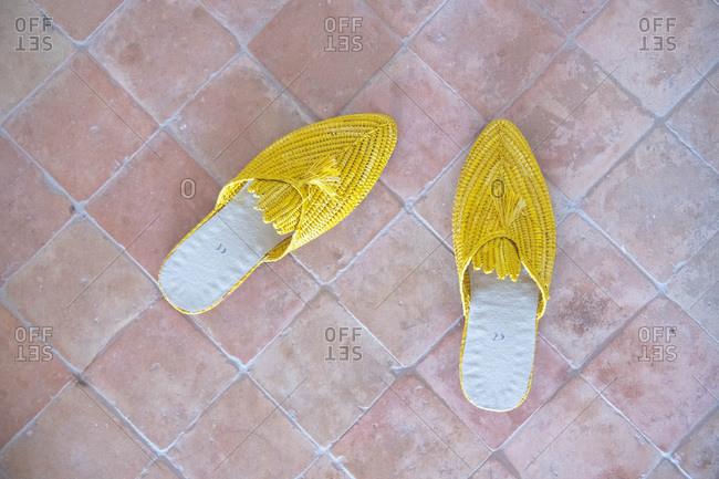 Yellow slippers on a brick floor