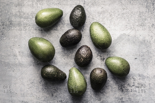 Assorted avocados laying in random group on neutral background