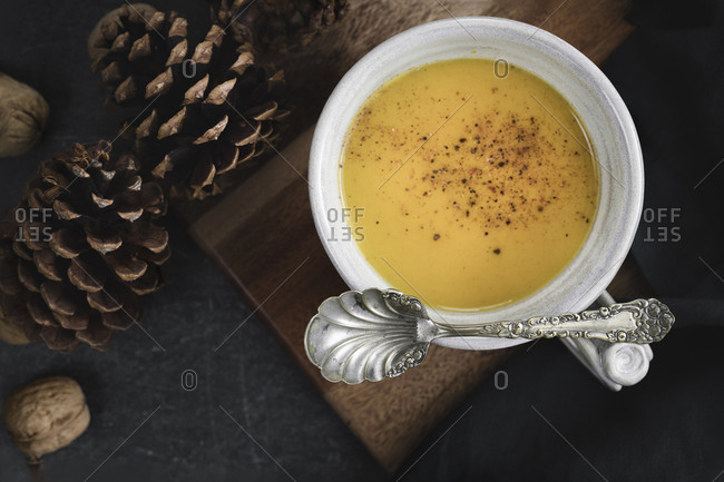 Butternut squash soup bowl with vintage spoon and pine cones, walnuts