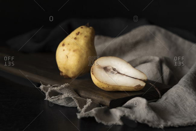 Aged pears on wooden board on linen, one cut, one whole