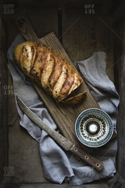 Artisan loaf of bread on board with knife, blue patterned bowl, linen