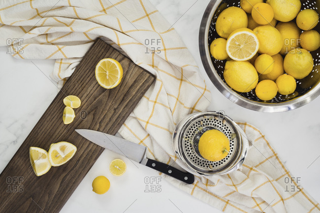 Colander full of whole lemons with cut lemons on board with knife