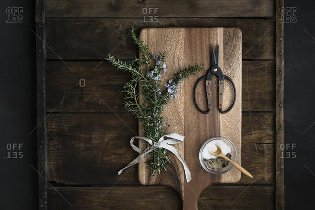Bundle of fresh rosemary, coarse salt, scissors on cutting boards