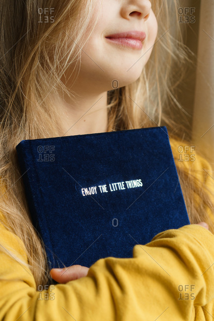 Young girl holding a book with text - enjoy the little things.