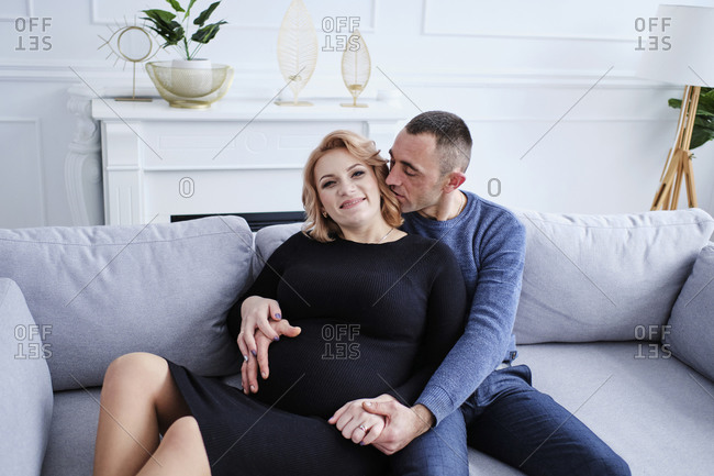 Expecting couple sitting together on the couch