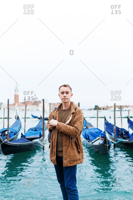 Young blond guy in a brown jacket in middle of streets of Venice