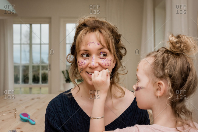 Mom and daughter playing with make up and dress up at home