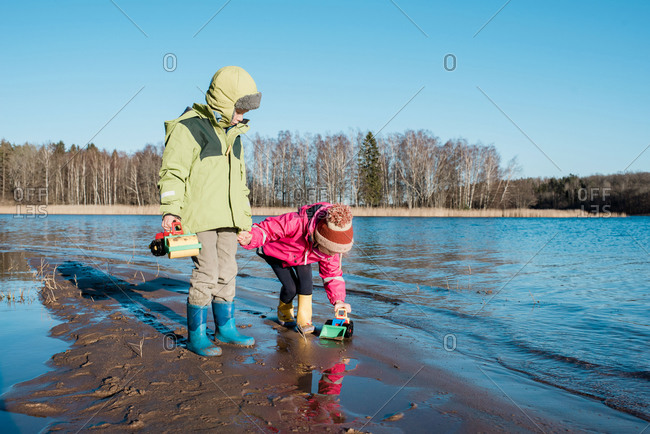Siblings holding hands at the beach whilst playing with toys
