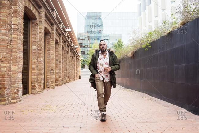 Bearded man walking across pathway holding a take away coffee