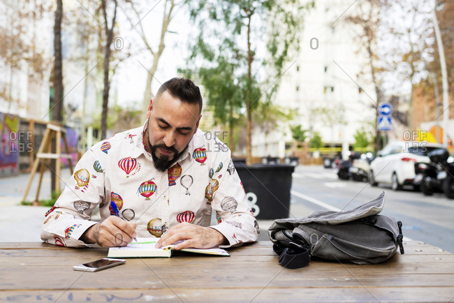 Bearded man sitting outdoors while working over a wooden table