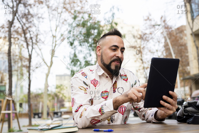 Young bearded businessman sitting at table, using tablet computer