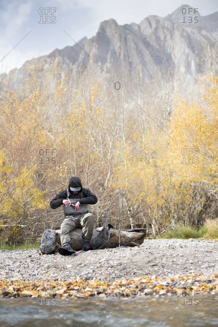 A fly fisherman prepares his gear in a beautiful mountain setting.