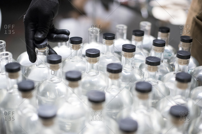 Bottles of liquor being capped at a distillery.