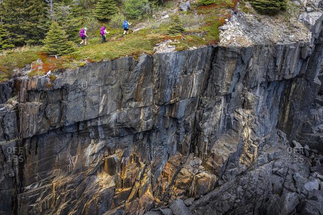 Three Backpackers Walk Along Cliff Edge On East Coast Trail