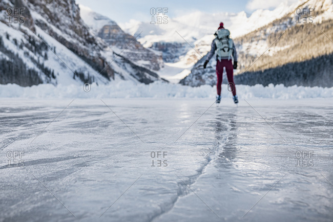 Young Woman Skating on Frozen Lake Louise in Banff Towards Mountains