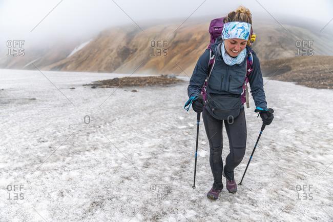 Female Backpacker Hiking Snow On Laugavegur Trail Near Landmannalaugar