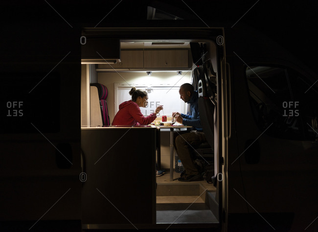 Couple having a relaxed dinner in a motorhome during a trip.