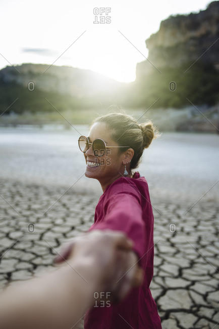 Smiling woman holding her hand for her boyfriend looking at the camera