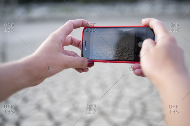 Close up of hands taking a photo with cellphone of landscape.