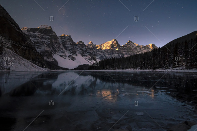 Moraine Lake at night under a starry sky