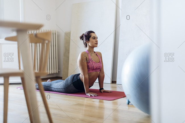 Focused ethnic woman practicing yoga at home