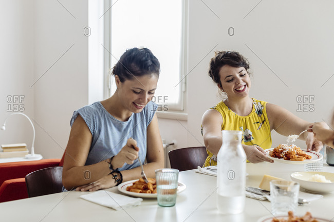 Cheerful women enjoying healthy dinner at home