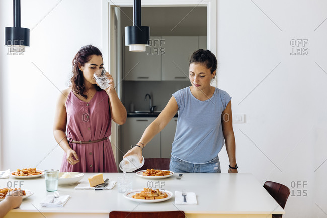 Women serving meal spending time at home together