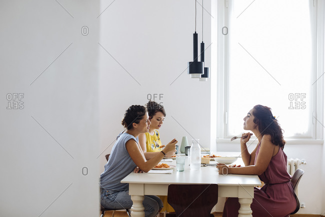 Content women chatting while enjoying dinner at home