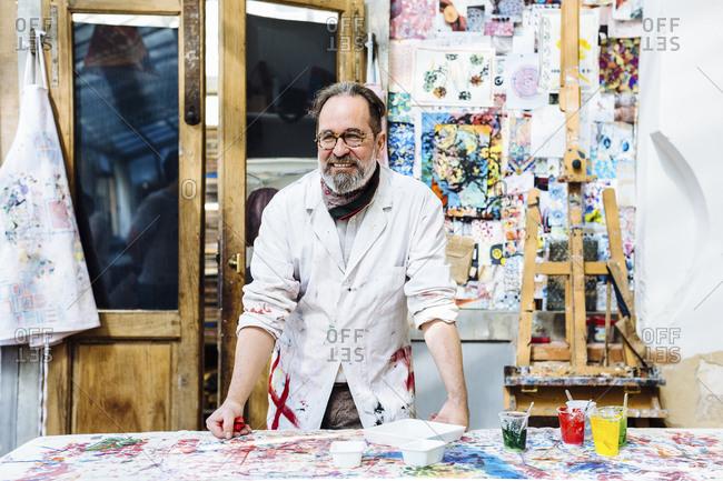 Cheerful mature artisan in textile workshop