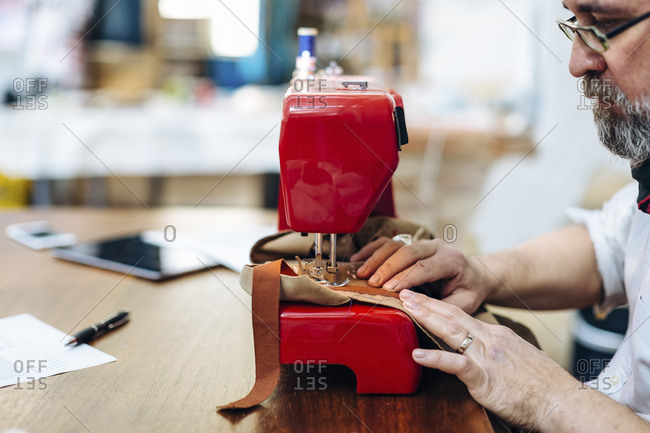 Focused male sewing material pieces on machine