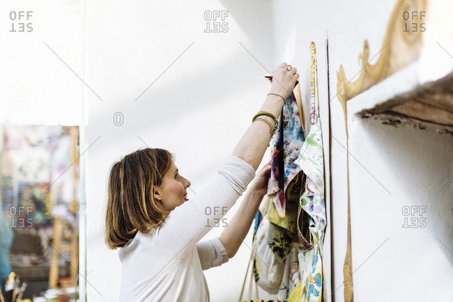 Female artisan hanging textile samples on wall in studio
