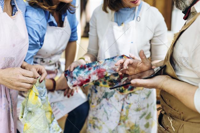 Crop artisans with gadget discussing textile design in workshop