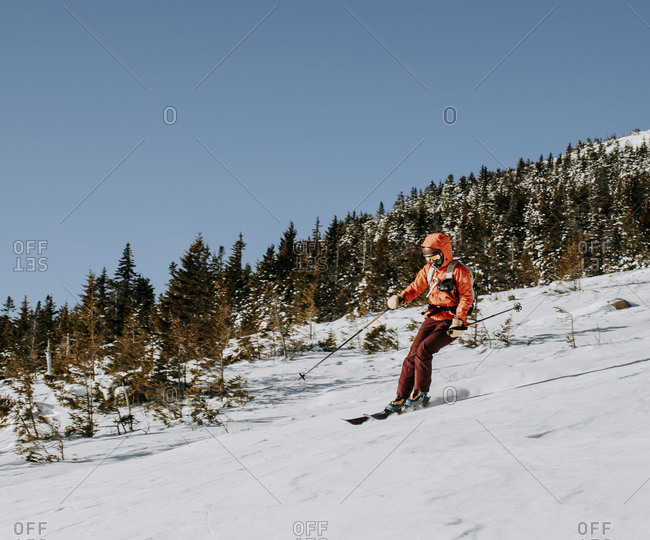 Female in red skis down Baldface Mountain, NH on a cold morning.