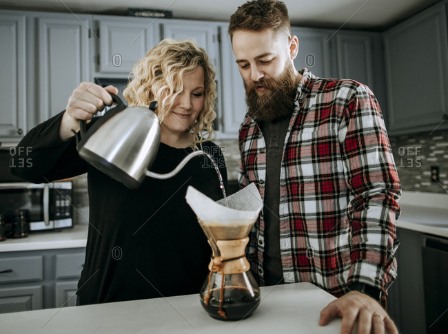 Smiling young couple make coffee in morning in their kitchen