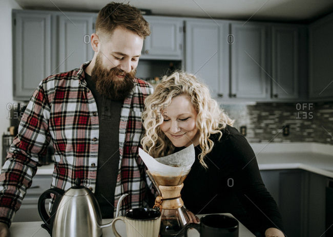 Young female smells morning coffee while husband with beard looks on