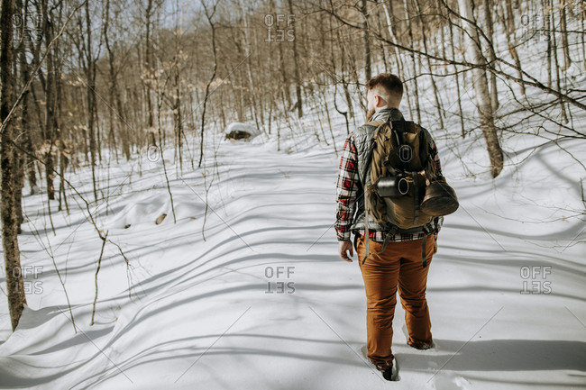 Man with canvas pack hikes through deep snow in the Maine woods