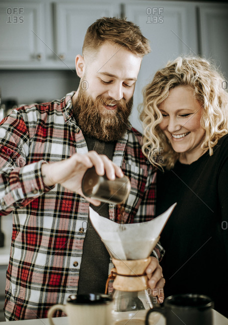 Man and woman smile as they prepare to make a coffee pour over