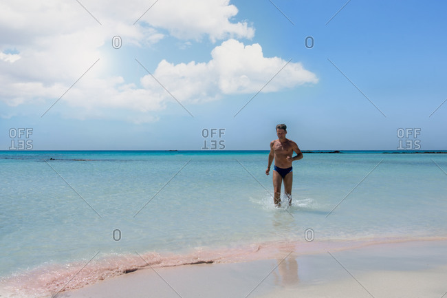 Landscape with sea and man enjoying water on Elafonisi beach in