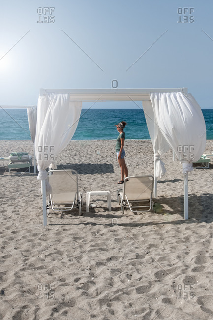 Woman looks at beach with loungers in Greece towards the horizon