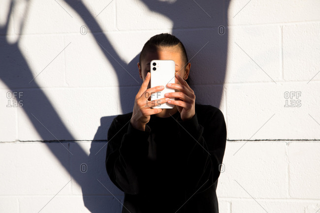 woman looking at cell phone with tree shadow