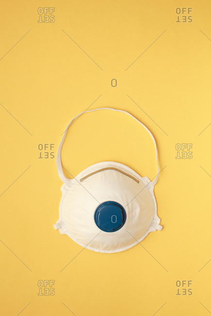 face mask or dust mask or filtering facepiece respirator - breathing protection against air pollution or flu or virus outbreak covid19 on yellow background