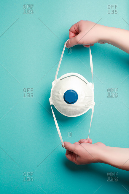 Hand holding mask sharing protective respirator. N95, FFP2, COVID-19, 2019-nCoV, virus protection, dust respirator concept.