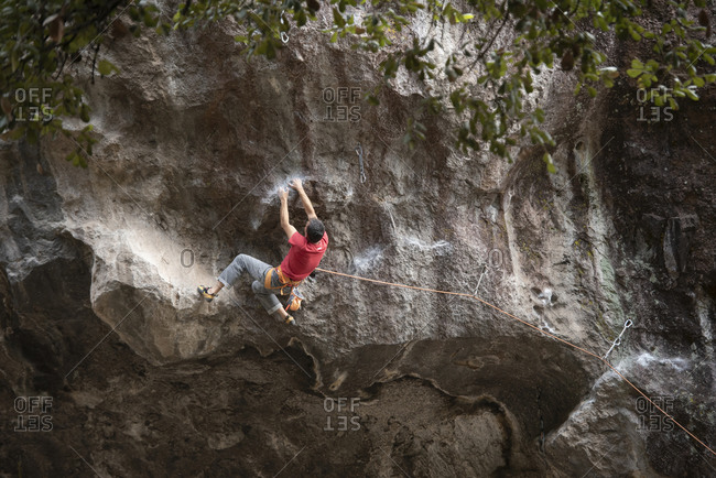 One man wearing red holds with both hands on rock wall while climbing