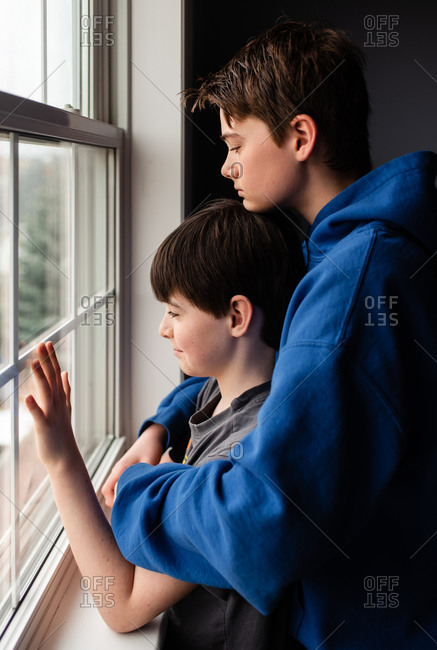 Two boys looking out of a window together with sad faces.