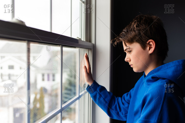 Tween boy looking out of a window in a dark room.