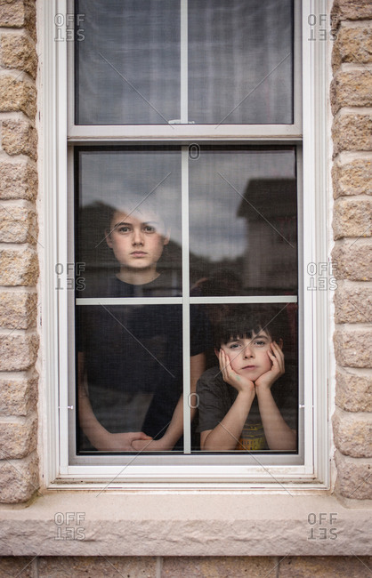 Two boys looking out of a window together with bored faces.